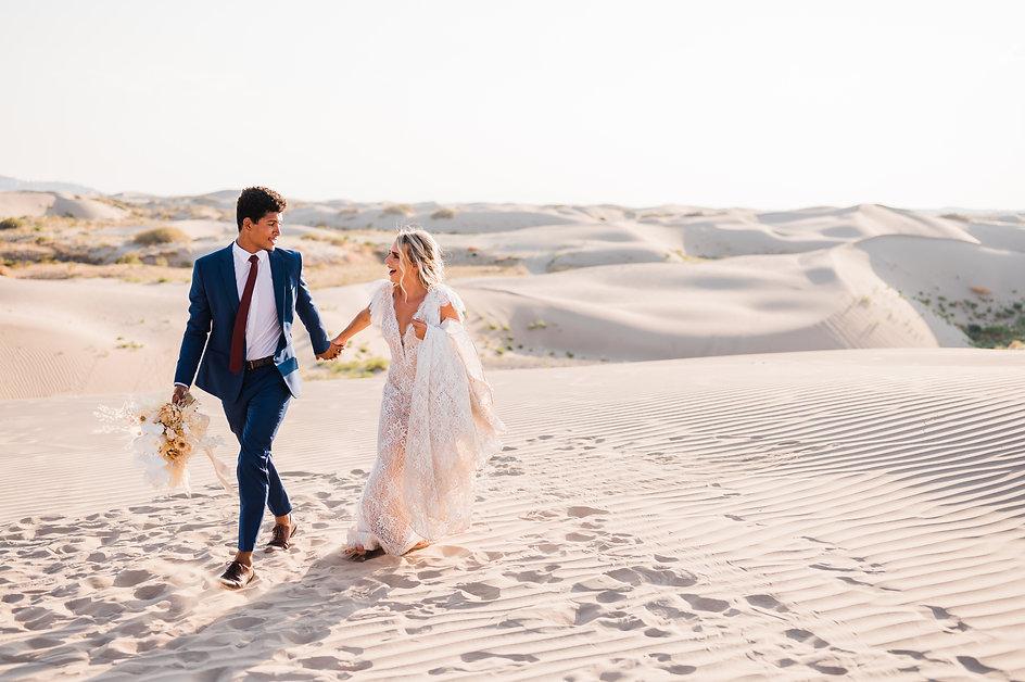 Couple runs through the Little Sahara Sand Dunes at their elopement