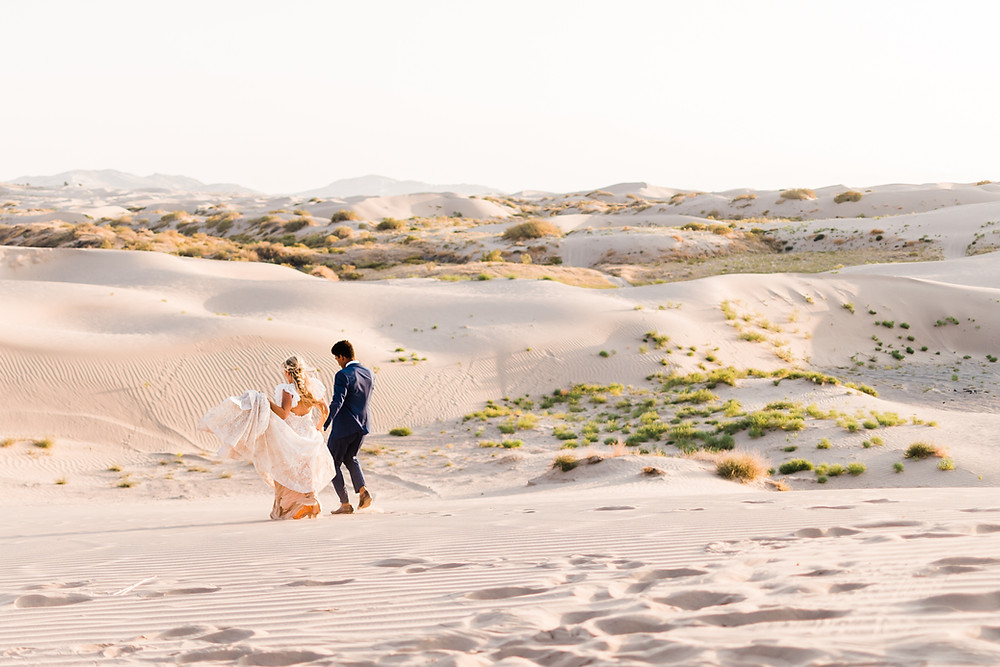 A man and woman in wedding attire run down the sand dunes of Utah at their elopement