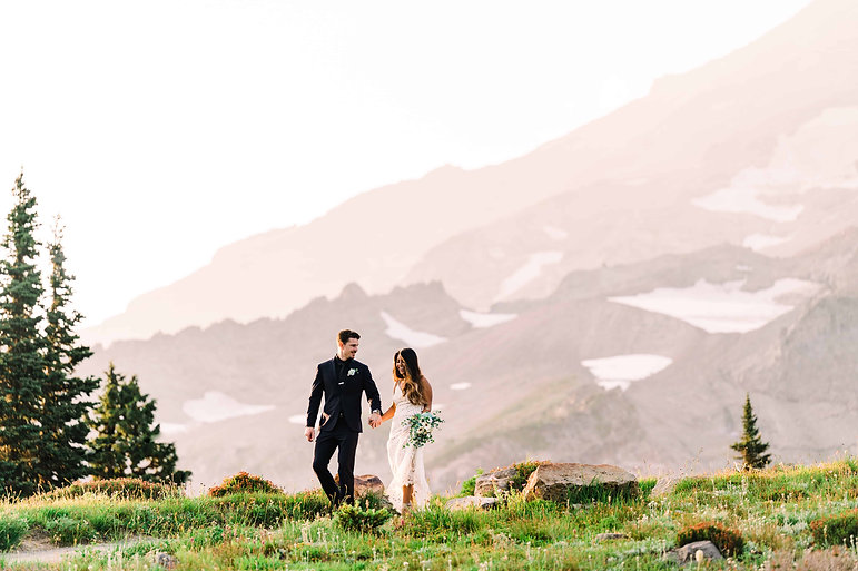 A man in a black suit smiles at his bride, as the hold hands and walk in front of Mt Rainier in Washington