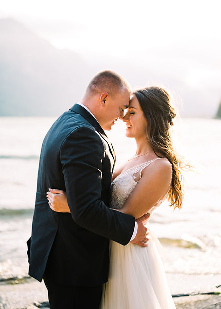 A man and woman embrace on the shore of a lake with mountains in the background. The man is in a dark suit, and the woman is smiling in a white wedding dress.