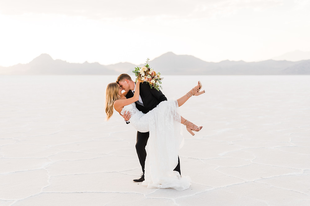 A bride is cradled in her husband's arms on their elopement day on the Bonneville Salt Flats