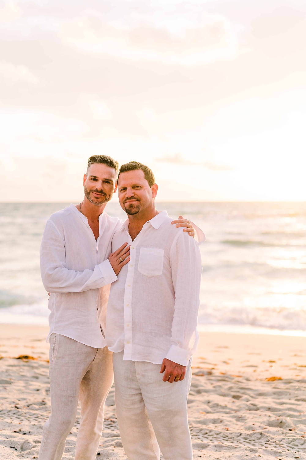 Two men have their arms around each other on the shore of a white sand beach at sunrise, wearing linen shirts at their elopement