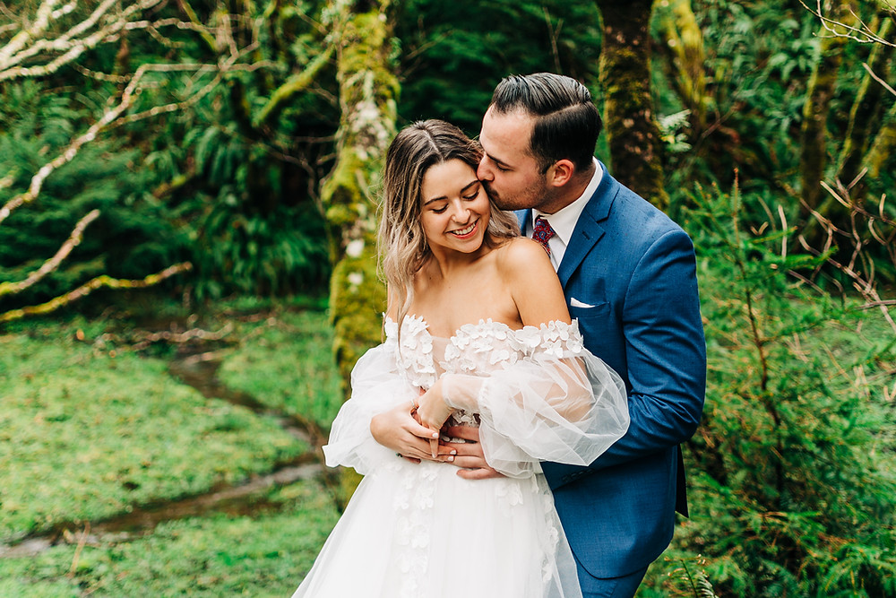 A couple embraces on their wedding day in a lush green forest in the Pacific Northwest