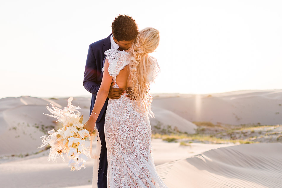 couple embraces at their elopement at the Little Sahara sand dunes