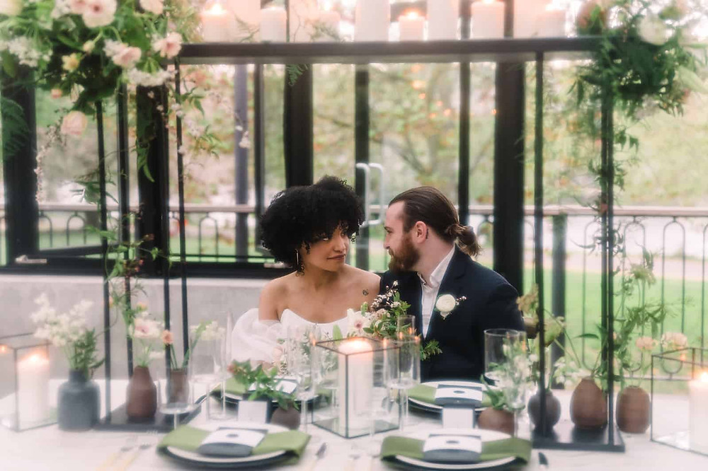 A couple gazes at each other on their elopement day, seated at a fancy table adorned with candles and flowers