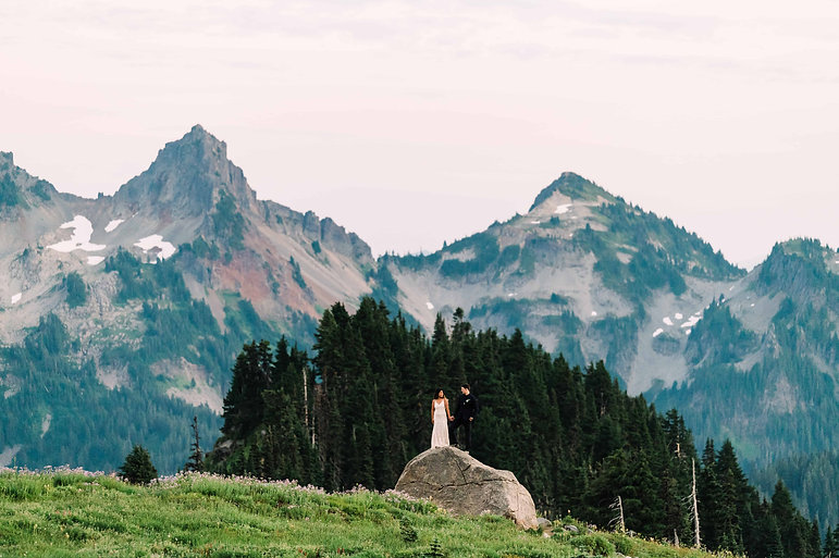 A man and woman stand atop a large rock in front of mountain peaks at North Cascades National Park