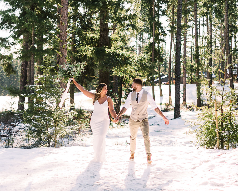 A man and woman in formal attire celebrate their winter elopement in the snow