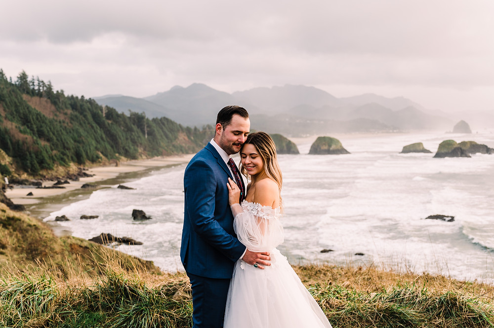 Man and a woman in a wedding gown embrace at Ecola State Park on the Oregon Coast