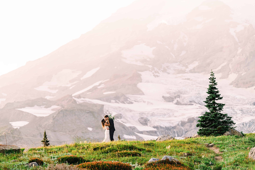 A man and woman kiss at the base of Mt. Rainier at their elopement