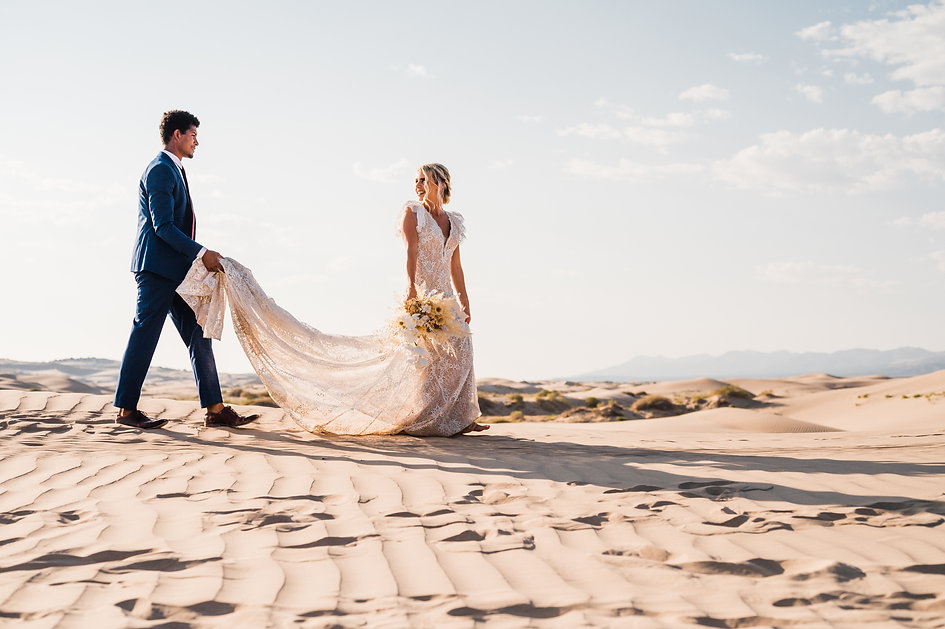 Bride in a lace dress leads her groom through the sand dunes on their elopement day at Little Sahara