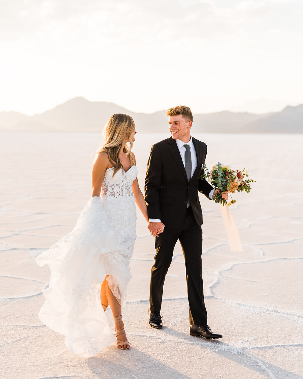 A man and woman in wedding attire are walking and laughing while looking at each other, the man is holding a bouquet