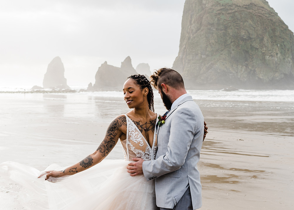 Interracial Couple embrace at their elopement at Cannon Beach in front of Haystack Rock