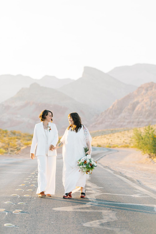 Gay women smile at their elopement on a street near a mountain range