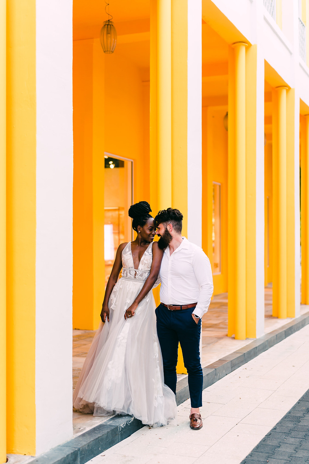 Interracial couple smiles at each other at their urban elopement