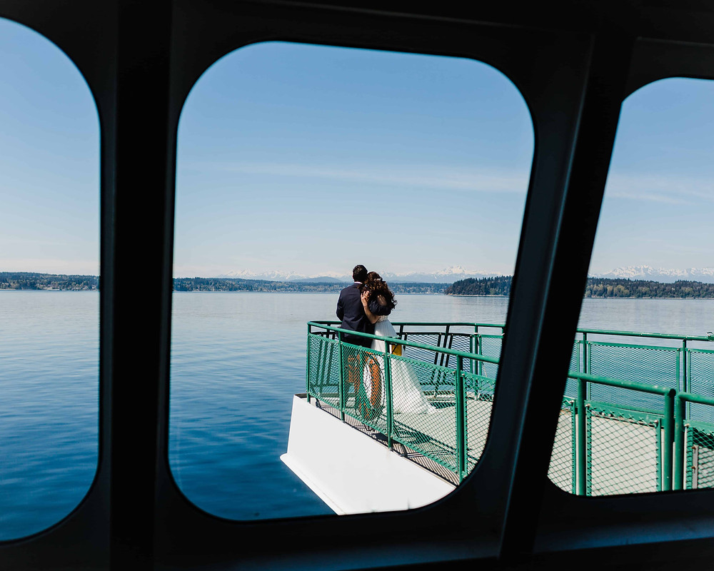 A view of a bride and groom embracing on the ferry to Vashon Island
