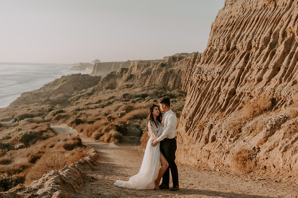 Couple in formal attire near dramatic cliffs at their elopement