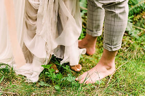 A couple's bare feet in the green grass of a Washington forest at their elopement
