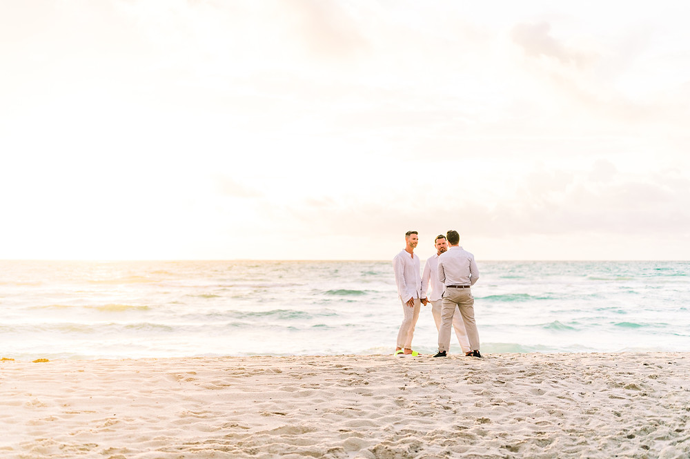 Three men in white shirts and tan pants stand on the shore on Miami Beach during an elopement ceremony at sunrise