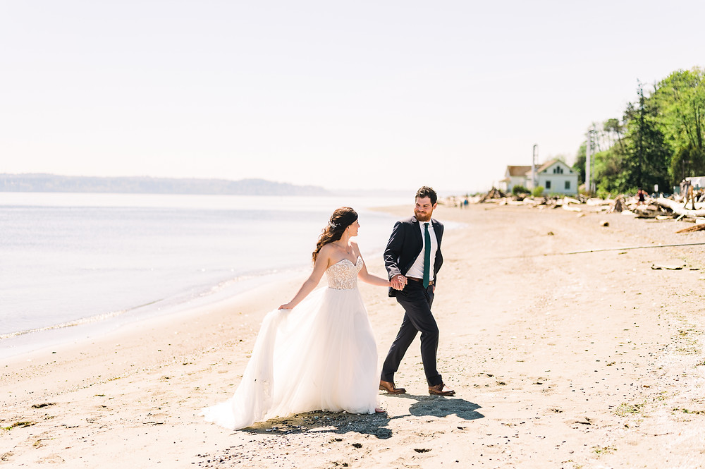 A white man and woman walk along the beach at their elopement