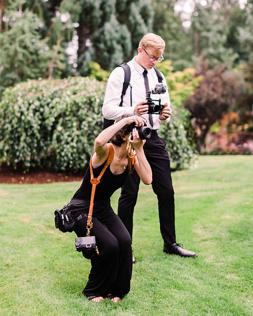 A washington elopement photographer in a black jumpsuit squats with her camera, photographing subjects off-screen