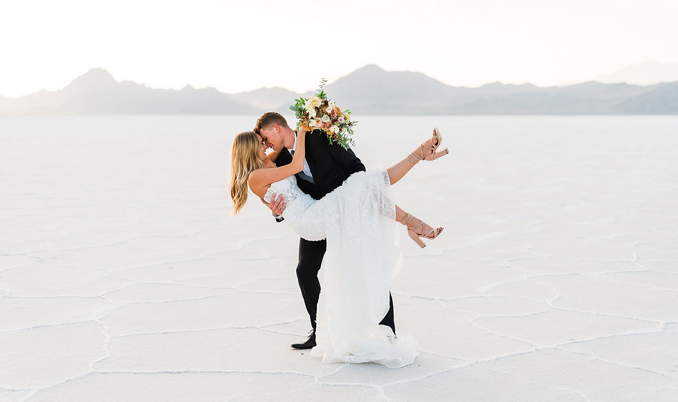Bride and groom holding each other smile at their elopement at the bonneville salt flats in utah