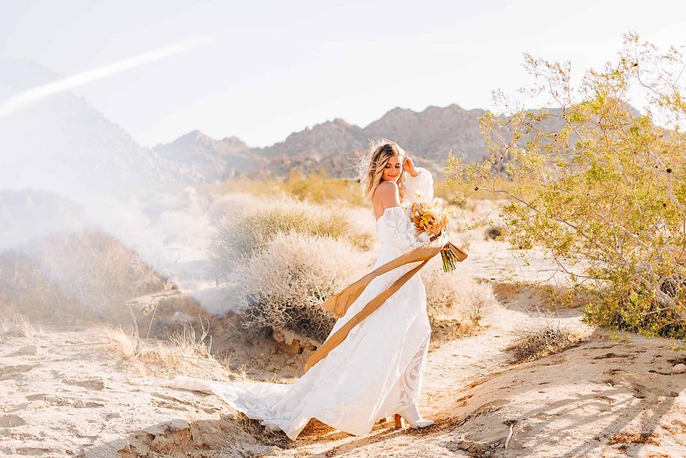 A blonde bride looks over her shoulder at her Joshua Tree elopement