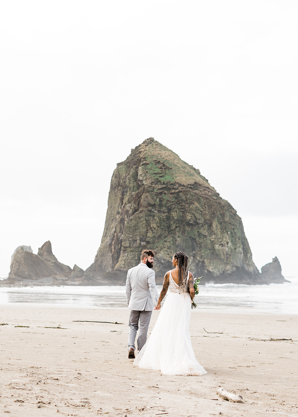 Man and Woman walk towards Haystack Rock at their Cannon Beach elopement