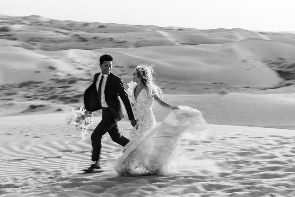 artistic photo of a couple running through sand dunes on their elopement day
