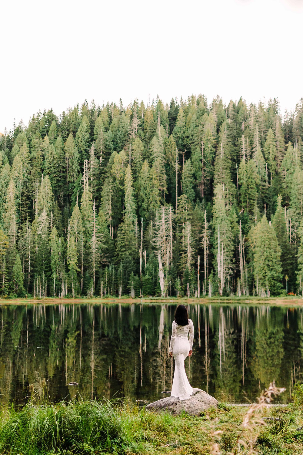 A thin, latina bride with black hair stands at the edge of a lake, with trees reflecting on the horizon line