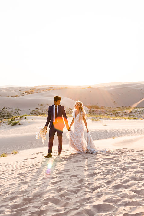 sun flare over a couple on their elopement day at the sand dunes