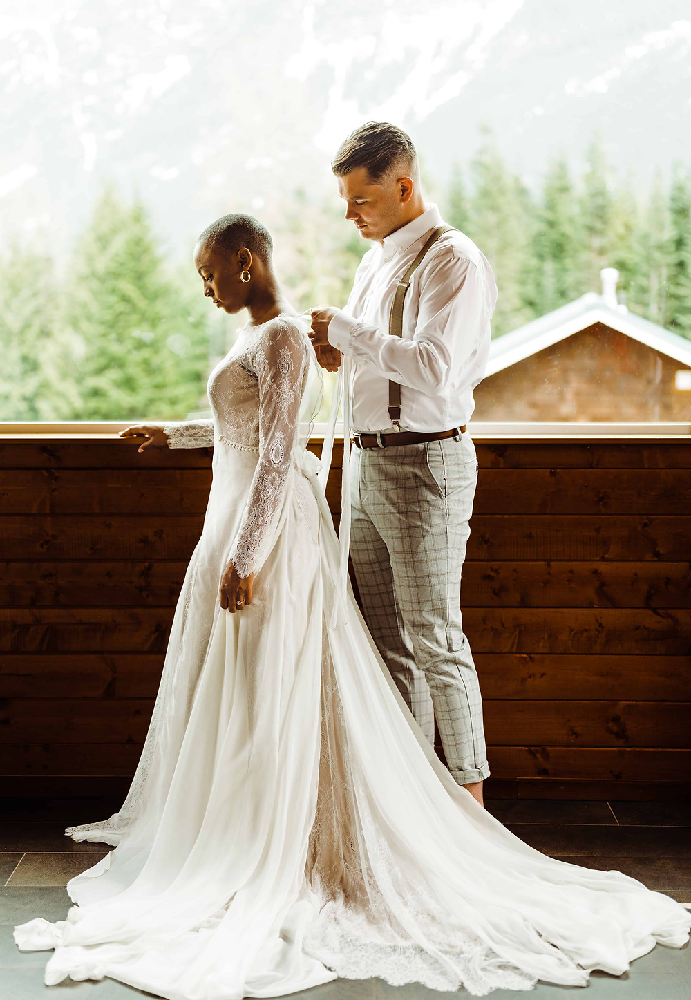A man in suspenders ties the back of his bride's wedding dress, the two of them in front of a window with thoughtful expressions