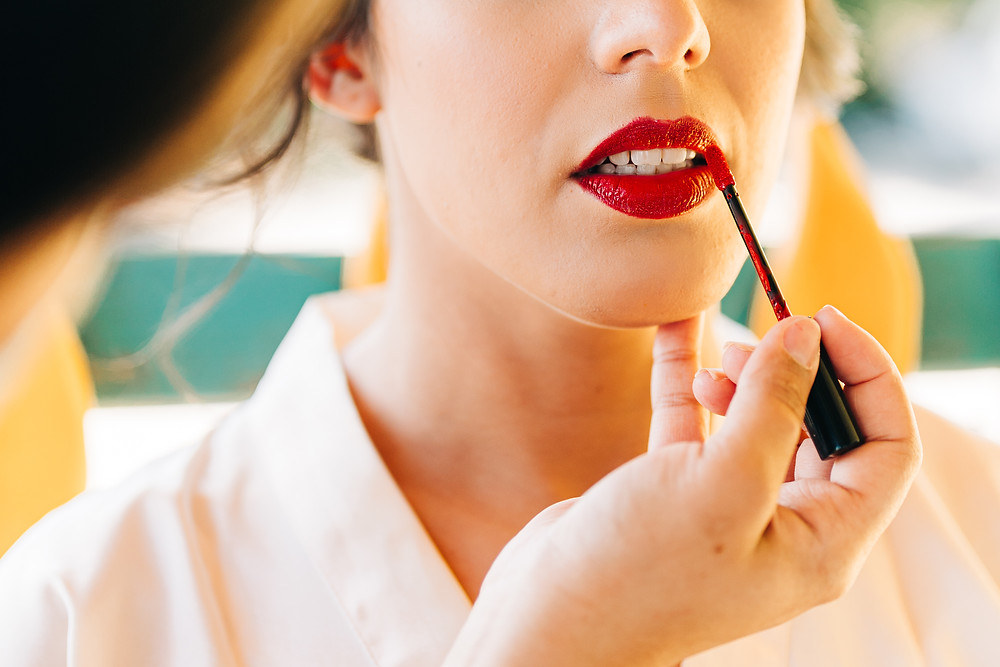 Close-up photo of a makeup artist applying lipstick at an elopement