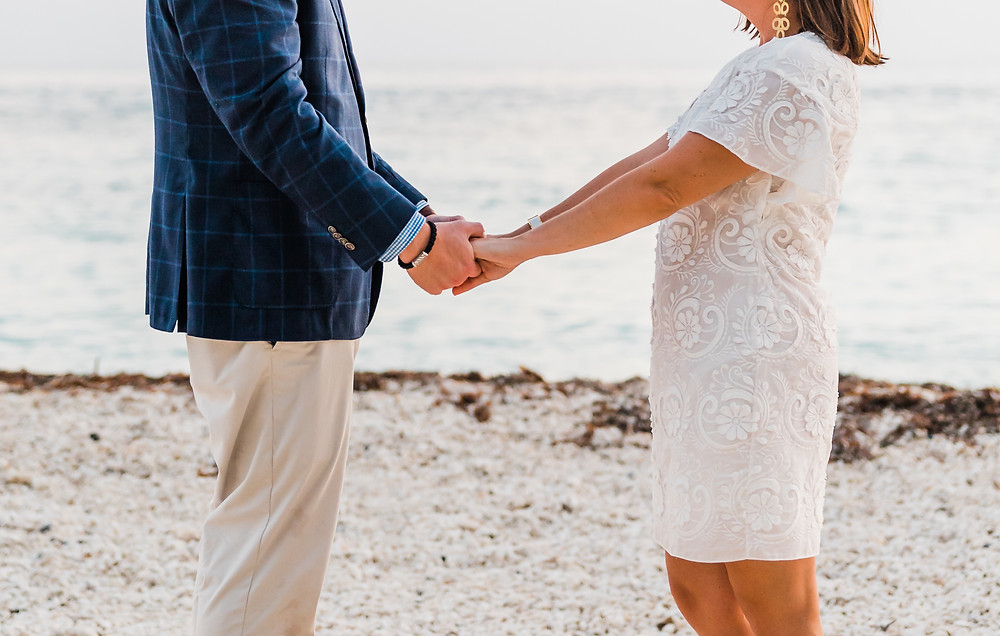 Man and woman hold hands at their proposal photoshoot