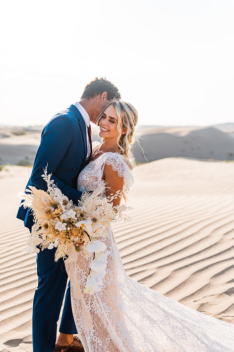 man makes his bride laugh at the Little Sahara sand dunes