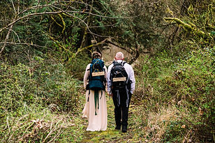 A man and woman in wedding attire walk away from the camera with hiking backpacks on, wearing signs that say Just Married