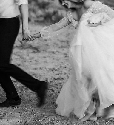 couple runs through the dirt at their adventure elopement