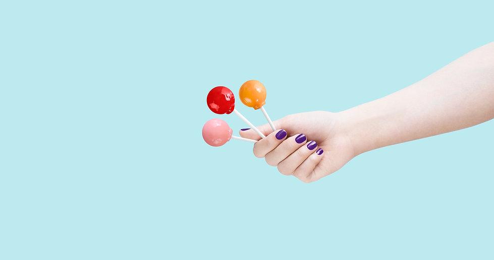 Hand holding three lollipops