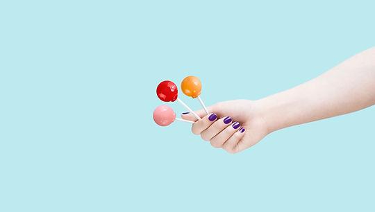 אישה מחזיקה שלוש סוכריות על מקל