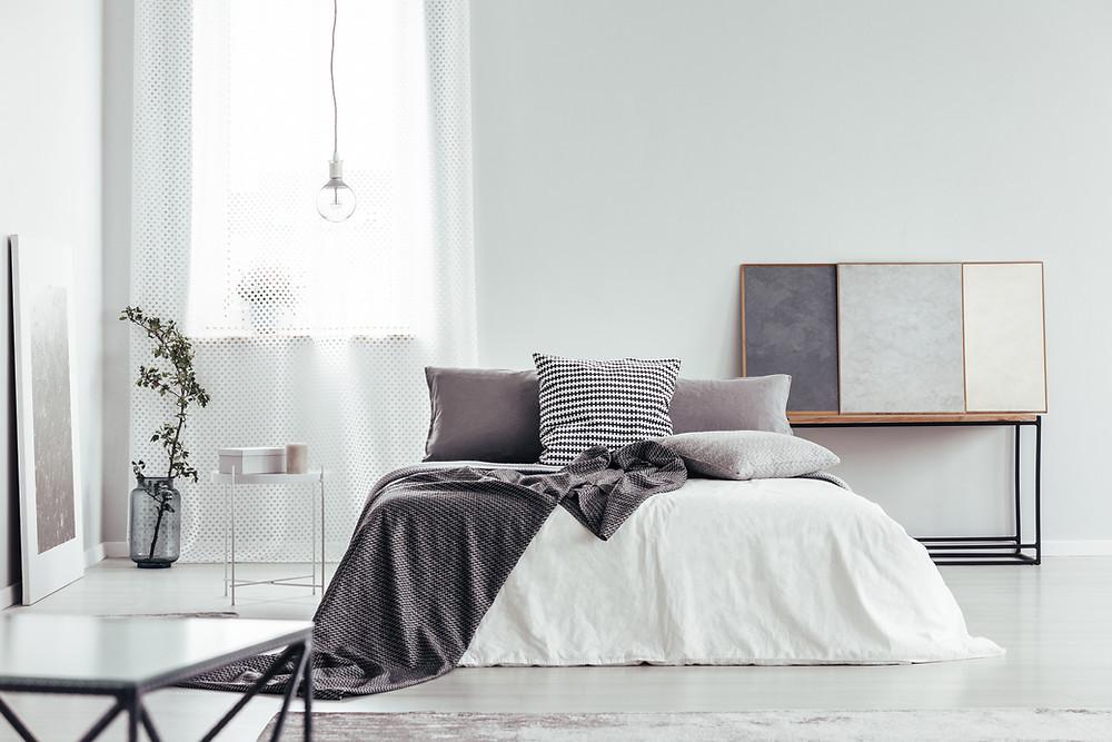 Ein minimalistisches Schlafzimmer mit Bett Eine ruhige Umgebung hilft dir schneller zu entspannen