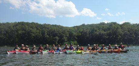group of paddlers on water in kayaks
