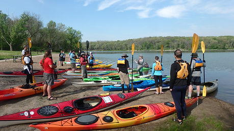 group of people around coloful kayaks on shore