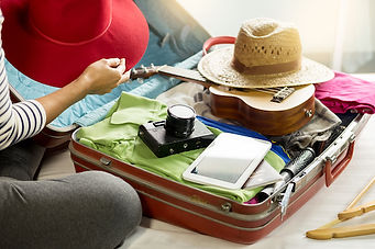 Woman hand packing a luggage for a new j