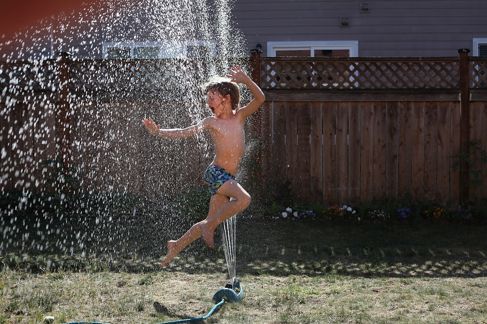 Boy playing in outdoor sprinkler