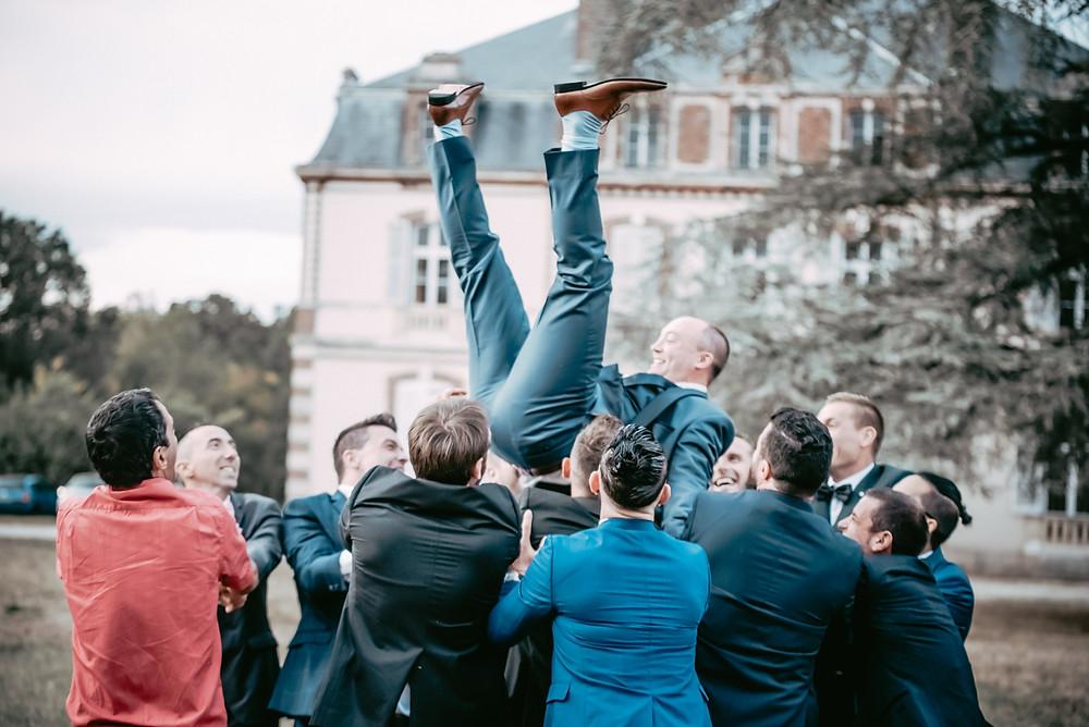 les invités lance le marié dans les l'air, joier et bonheur sur le visages des convives. c'est la fête ils en profitent.