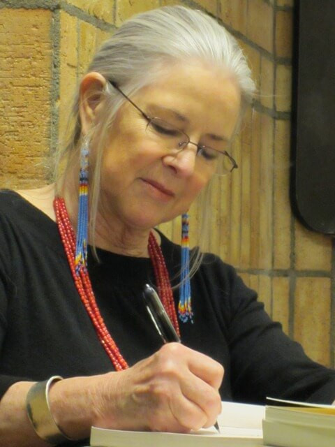 Linda Hogan signing a copy of one of her books, image courtesy of the Native Arts and Cultures Foundation