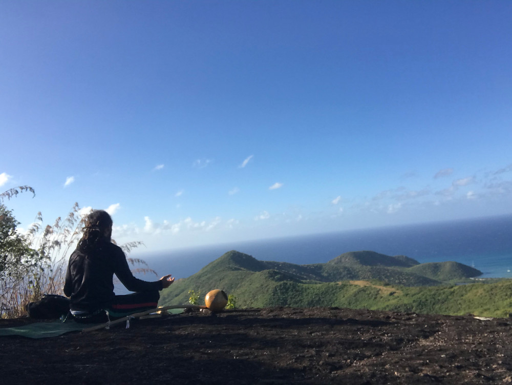 Man sitting on yoga mat at the top of Antigua's Signal Hill