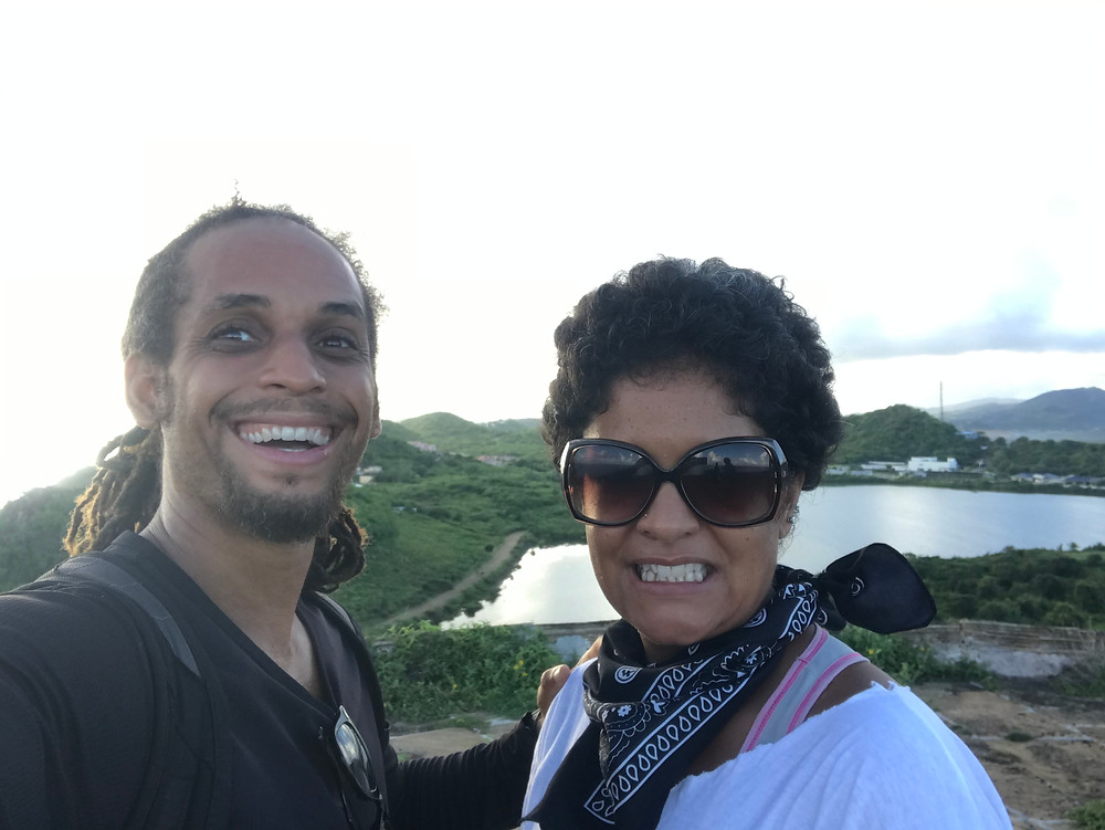 Two people smiling at the top of an Antiguan hill