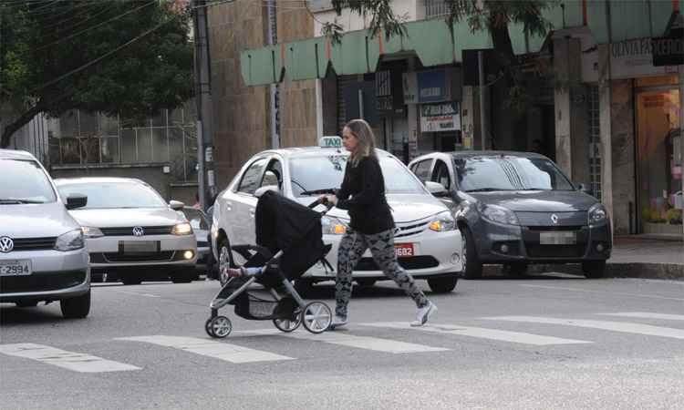 Travessia de mulher com carrinho de bebê na faixa de pedestres