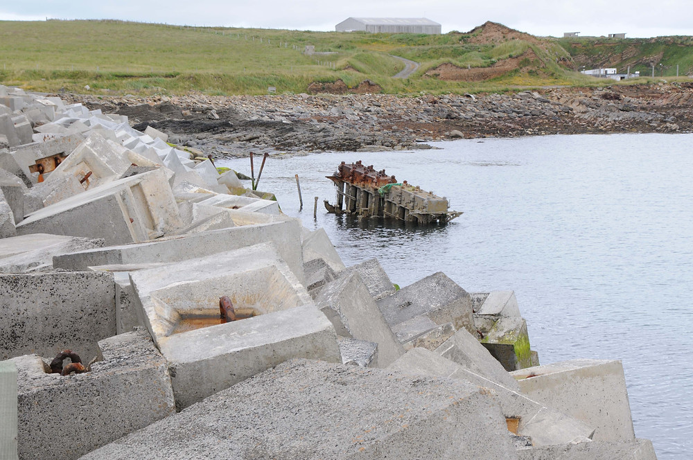 The concrete blocks of the Churchill Barriers with the remains of a blockship beyond