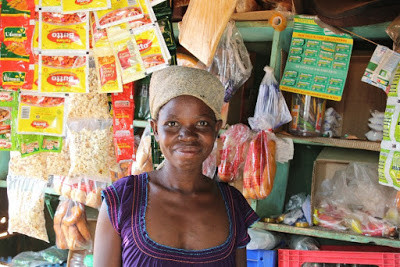 A woman in front of the inventory she was able to add to her shop because of a microfinance loan